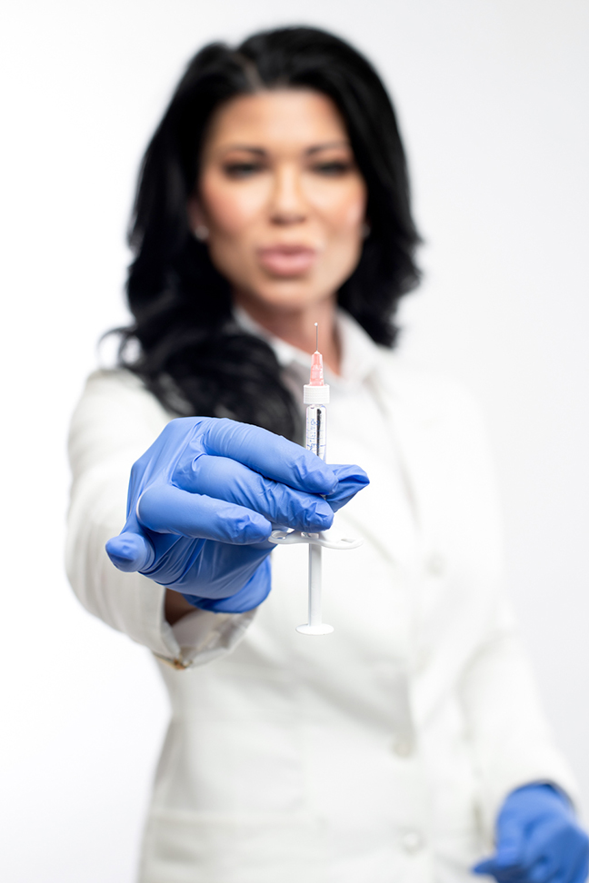 Image of esthetician holding tools with blue gloves.