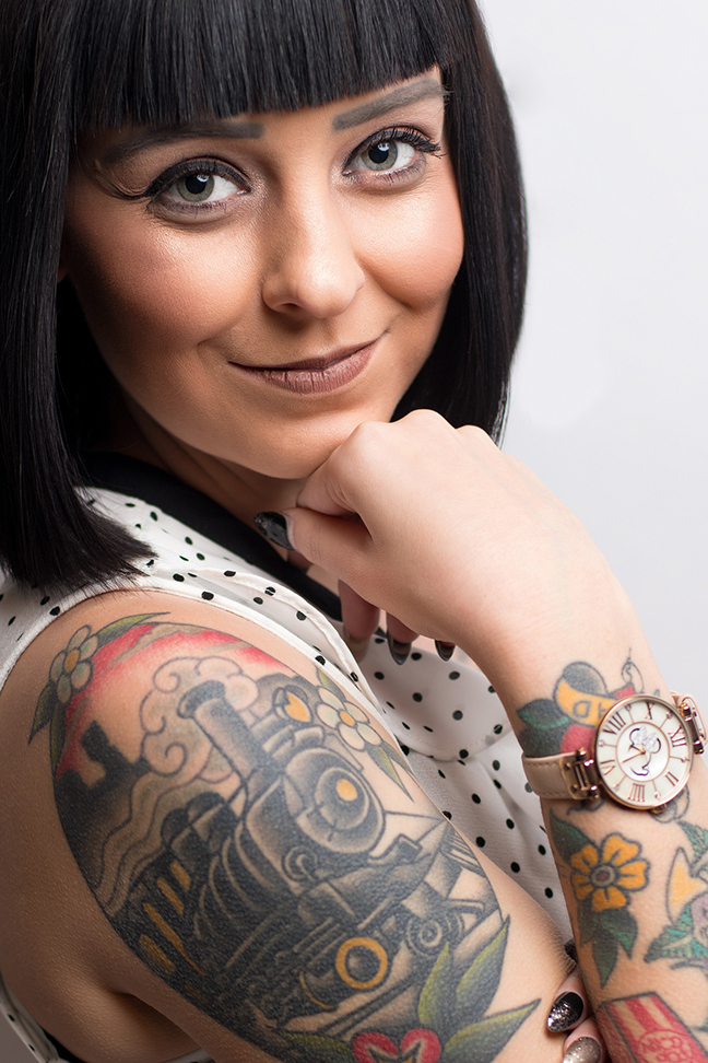 Close up portrait of woman smiling with watch on wrist.