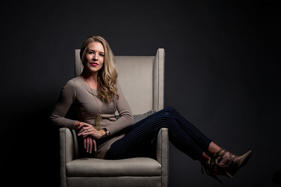 Portrait of woman posing in tall chair with dramatic lighting.