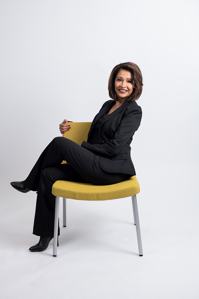 Portrait of woman sitting in yellow chair smiling.