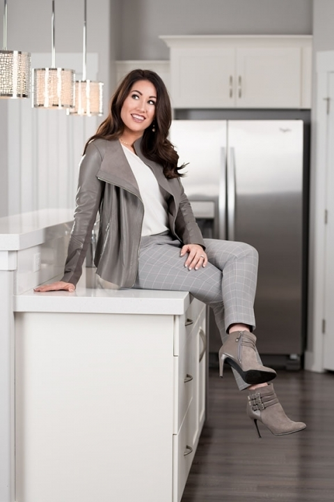 Full length portrait of woman sitting on countertop in new kitchen.