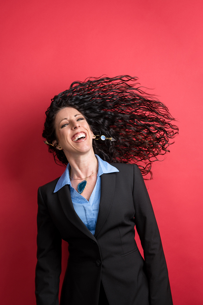 Headshot of woman flipping her hair on red background.