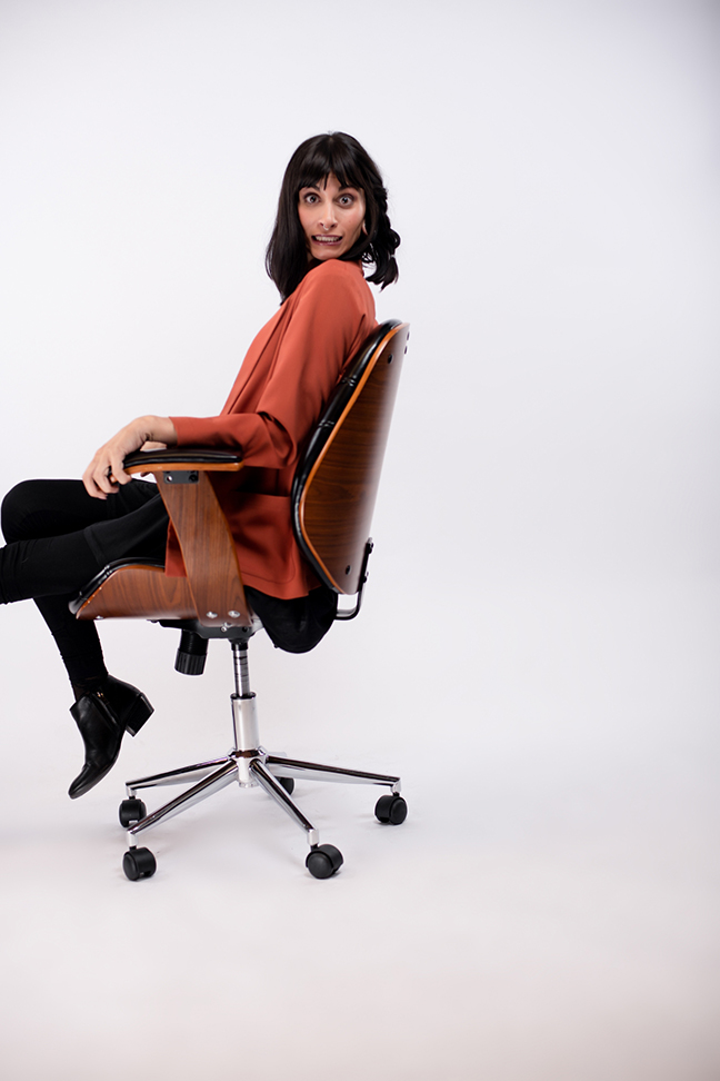 Woman sliding backward in chair smiling for picture.