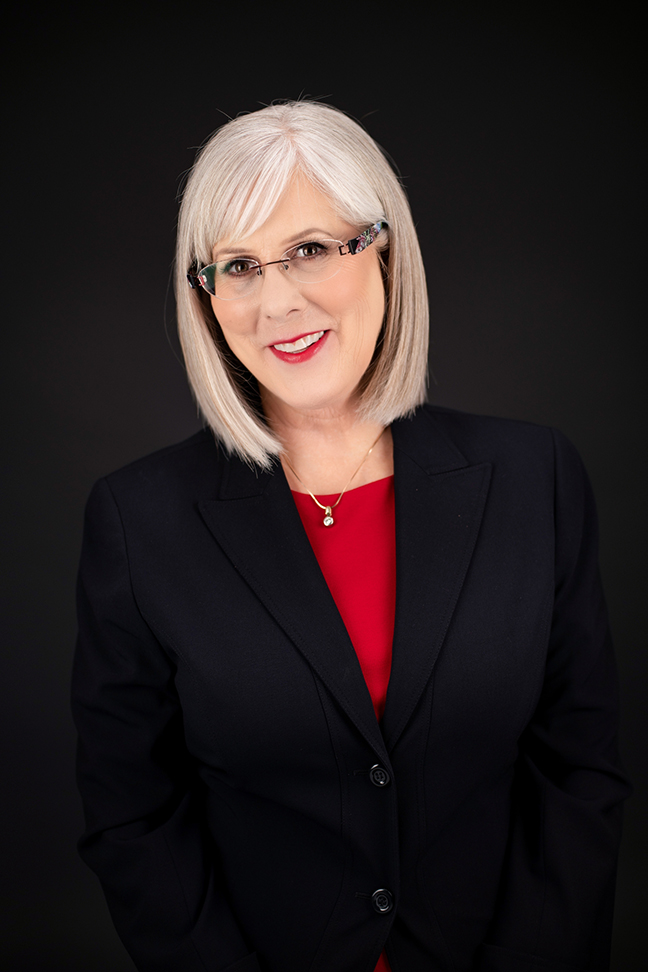 Woman with glasses smiling for headshot.