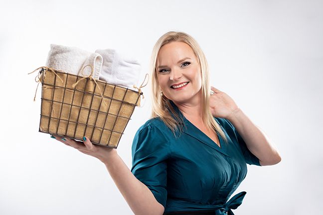 Esthetician holding basket of towels.