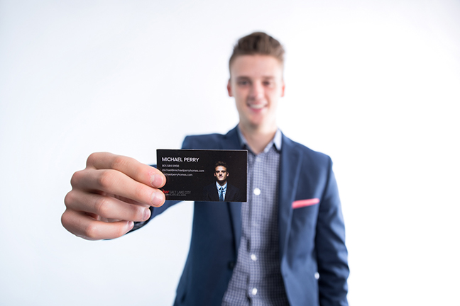 Branding headshot of man with focus on business card.
