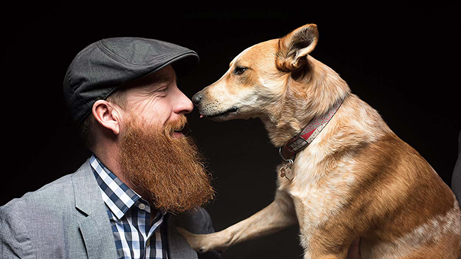Head shot of bearded man with dog.