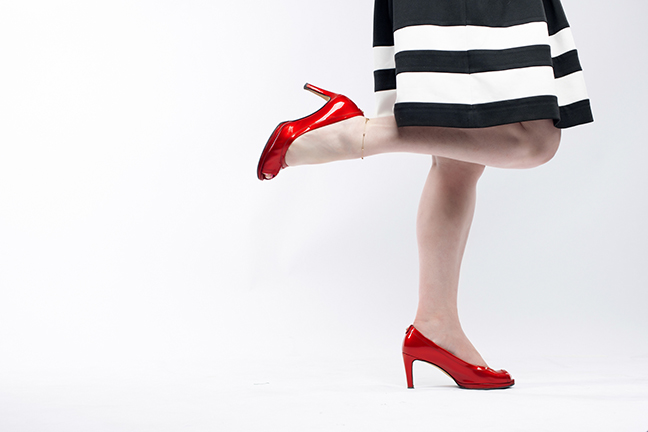Portrait of woman dressed featuring bright red shoes.